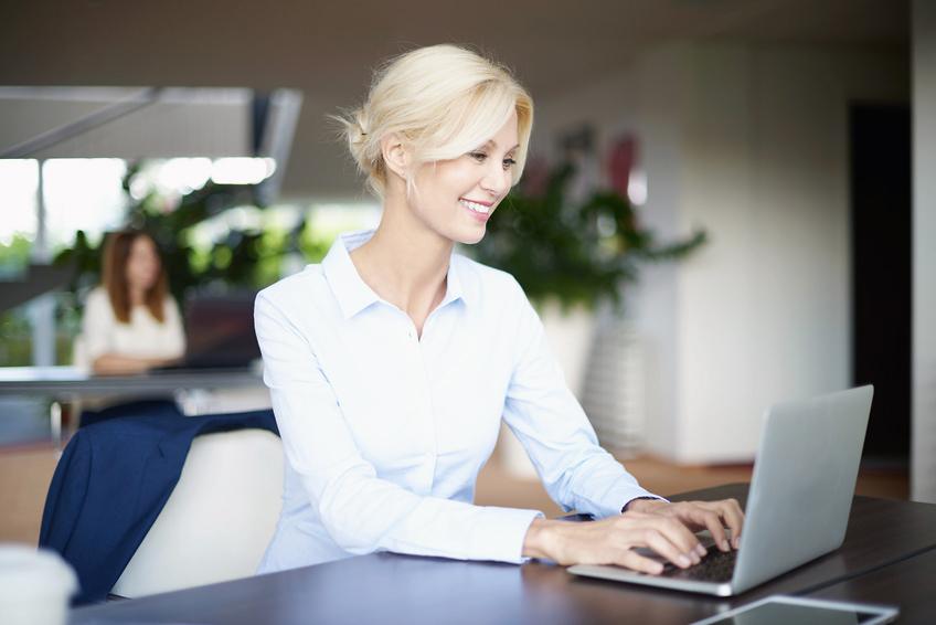 Foto einer blonden Frau am Laptop
